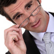 Stock Photo: Young businessmremoving glasses