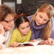 Three generations reading a book together — Stock Photo