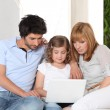 Young family gathered on the sofa with laptop - Stock Photo