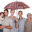 Family under umbrella — Stock Photo