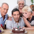 Woman blowing birthday candles in family — Stock Photo #10197879
