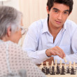 Stock Photo: Grandmother and grandson playing chess