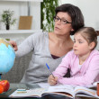 Mother and young daughter doing her homework — Stock Photo