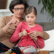 Woman teaching how to knit to little girl — Stok fotoğraf