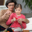 Stock Photo: Womteaching how to knit to little girl