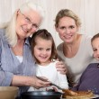 Grandmother making crepes surrounded by daughter and grandchildren — Stock Photo