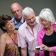 Two elderly couple looking at photos on digital camera — Stock Photo