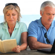 Young couple with book and computer — Stock Photo