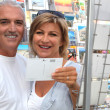 Stock Photo: Mature couple looking at postcards