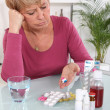 Middle-aged woman taking her medication — Stock Photo