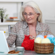 Older woman knitting at a laptop — Stock Photo