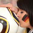 Young german brunette kissing soccer ball — Zdjęcie stockowe