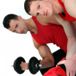 Muscular fellow lifting weight and guy with boxing gloves - Stockfoto