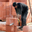 Builder cutting blocks to size - Stock Photo