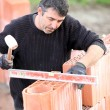 Builder using a spirit level - Stock Photo