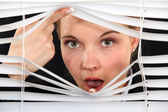 Nosy blond woman peering through blinds — Stock Photo