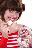 Woman eating marshmallows out of jar — Stock Photo
