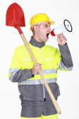 Construction with shovel shouting into megaphone — Stock Photo
