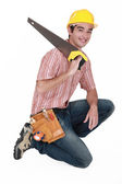 Carpenter with saw kneeling — Stock Photo