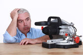 Man with circular saw looking fed-up — Stock Photo