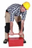 Bouwer worstelen te heffen zware gereedschapskist — Stockfoto