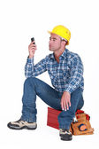 Man sat on tool box sending text message — Stock Photo