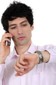 A businessman over the phone looking at his watch. — Stock Photo