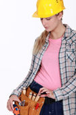 Tradeswoman pulling a tool from her belt — Stock Photo