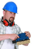 Mason demonstrating power sander — Stock Photo