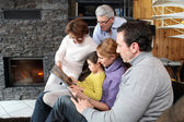 Family at home around a fireplace — Stock Photo