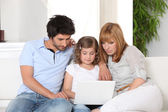 Young family gathered on the sofa with laptop — Stock Photo