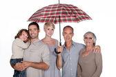 Family under umbrella — Stock Photo