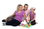 Parents watching their daughter play with blocks — Stock Photo
