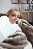 Woman snug on a sofa — Stock Photo
