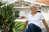 Old woman in her front garden — Stock Photo