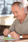 Elderly man drinking a cup of coffee — Stock Photo