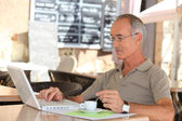 Senior man drinking coffee and checking his e-mails — Stock Photo