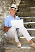 Senior ma n relaxing outdoors with his laptop — Stock Photo