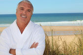 Man in bathrobe on the beach — Stock Photo