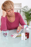 Middle-aged woman taking her medication — Stok fotoğraf