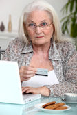 Grandmother shopping online — Stock Photo