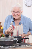 Old woman cooking — Stock Photo