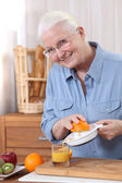 Elderly woman pouring freshly squeezed orange juice — Stock Photo