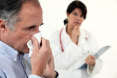 Man blowing his nose next to a doctor — Stock Photo