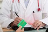 Patiënt betalen voor een medische raadpleging — Stockfoto