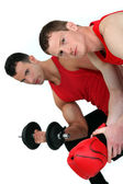 Muscular fellow lifting weight and guy with boxing gloves — Stock Photo