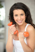Woman with orange weights — Stock Photo
