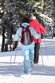 Middle-aged couple cross-country skiing — Stock Photo