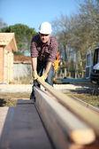 Carpenter arranging wooden beans on work-site — Stock Photo