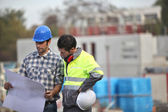 Two site workers sticking to the plans — Stock Photo